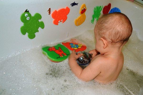 Малыш, который уверенно сидит заинтересуется цветными принадлежностями для игры в ванночке. Воспользуйтесь этим и займите ребенка на время процедуры